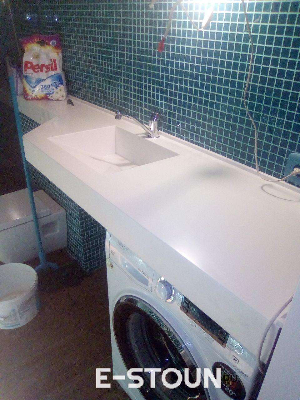 Столешница в ванную комнату из камня: накрывает стиральную машинку и сужается к дальней стенке